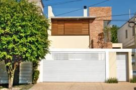 Portão branco contrasta com a madeira utilizada no primeiro andar